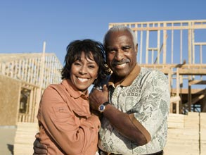 Middle aged couple embracing in front of a construction site