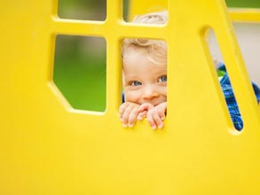 Young child playing peek-a-boo behind a large yellow window