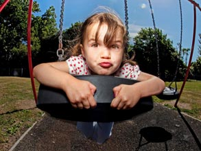 Young girl riding a tire swing